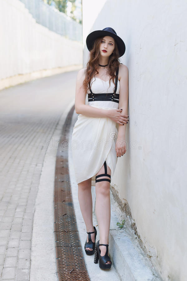 Young beautiful woman wearing trendy outfit, white dress, black hat and leather swordbelt. Longhaired brunette stock photography