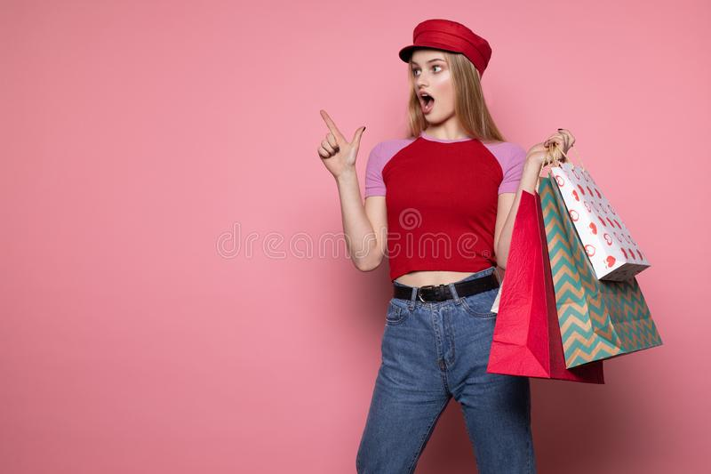 Young beautiful shocked girl in red hat with colorful shopping bags pointing up with finger, looking away stock photo