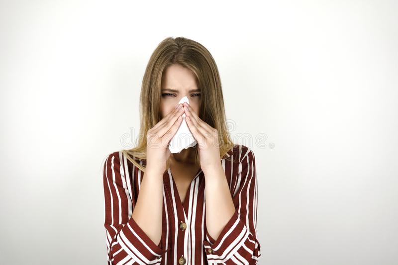 Young beautiful sick blonde woman wearing trendy striped shirt blowing her nose isolated white background stock images
