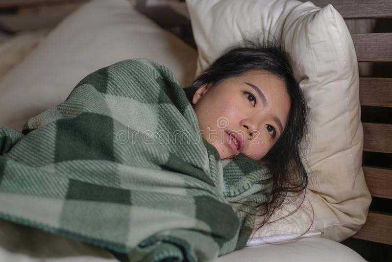 Young beautiful sick and exhausted Asian Chinese woman suffering cold and flu having temperature lying on bed covering with. Lifestyle portrait of young royalty free stock photo