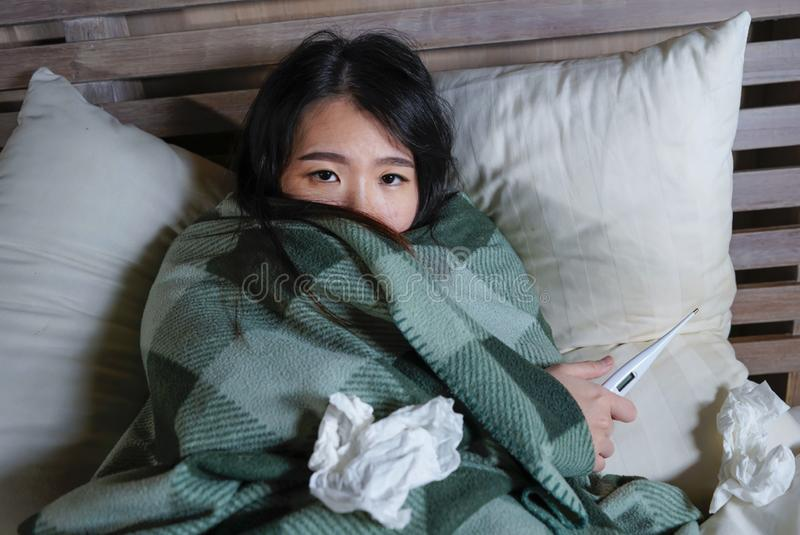 Young beautiful sick and exhausted Asian Chinese woman suffering cold and flu holding thermometer having temperature lying on bed. Lifestyle portrait of young royalty free stock photo