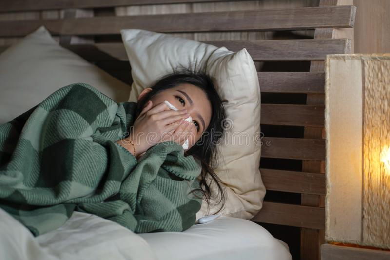 Young beautiful sick and exhausted Asian Japanese woman suffering cold and flu having temperature lying on bed covering with. Lifestyle portrait of young royalty free stock photography