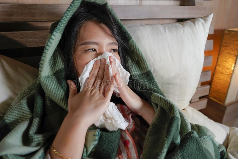 Young beautiful sick and exhausted Asian Korean woman suffering cold and flu having temperature lying on bed covering with blanket. Lifestyle portrait of young royalty free stock photos