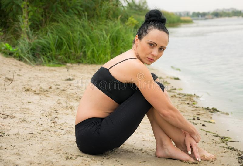 Young woman doing yoga on the river bank. City break royalty free stock photo