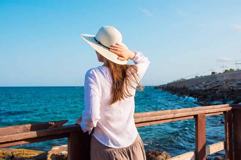 Young beautiful slender woman in sunhat with long hair in boho style clothes at the shore looking and the sea clear blue sky. Rocks, tranquility, harmony royalty free stock photo