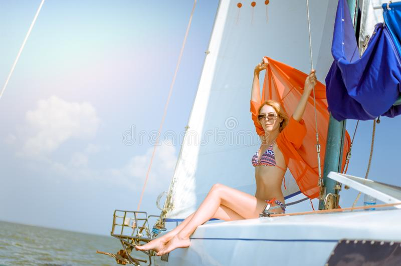 Young beautiful slim sexy girl in bikini and pareo is resting on cruise on a private sailing yacht royalty free stock photography