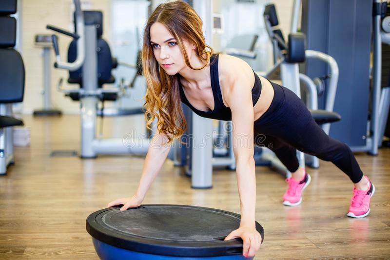 Young beautiful slim woman doing push ups with bosu ball in gym. stock photos