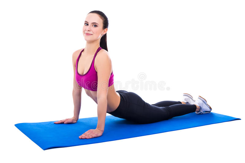 Young beautiful slim woman doing stretching exercises on yoga ma royalty free stock image