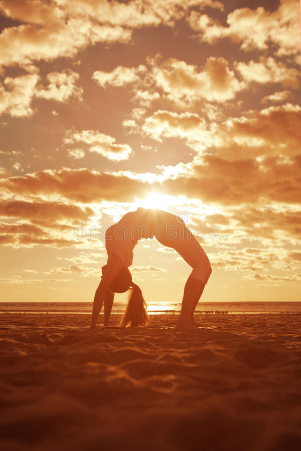 Young beautiful slim woman silhouette practices yoga on the beach at sunset. Yoga at sunrise stock image
