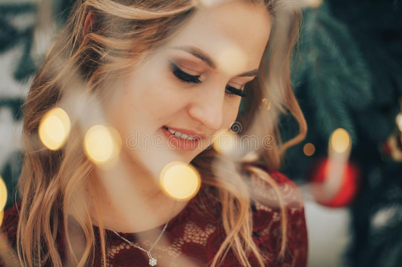 Young beautiful smiles woman through the lights of the garland royalty free stock image