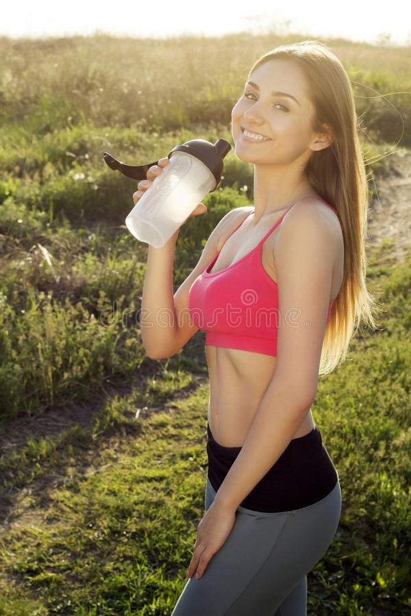 Young beautiful smiley woman doing sport exercises and drinking. Water stock images