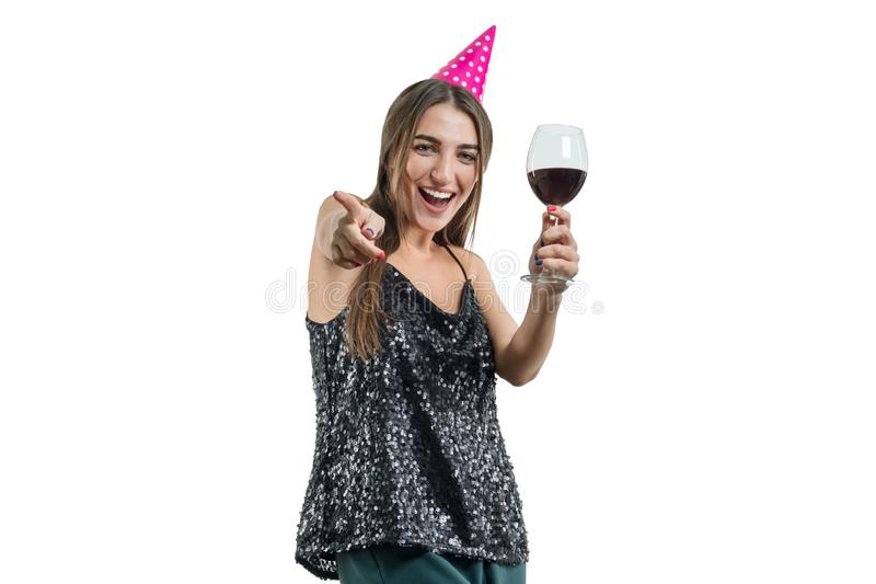Young beautiful smiling brunette woman with glass of red wine and wearing party hat points her finger at you, isolated on white stock image