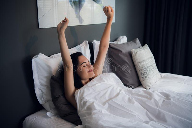 Young beautiful smiling and brunette woman lying in bed trying to wake up early morning stretching hands after sleep stock image
