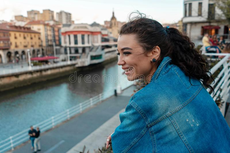 Young beautiful smiling woman at street near river in European old town. Travel blogger. Freedom and freelancer royalty free stock image