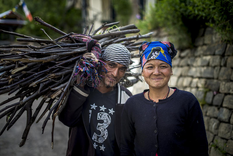 Young beautiful smiling couple walk on street. Man carry bunch of branches, Himachal Pradesh. stock photo