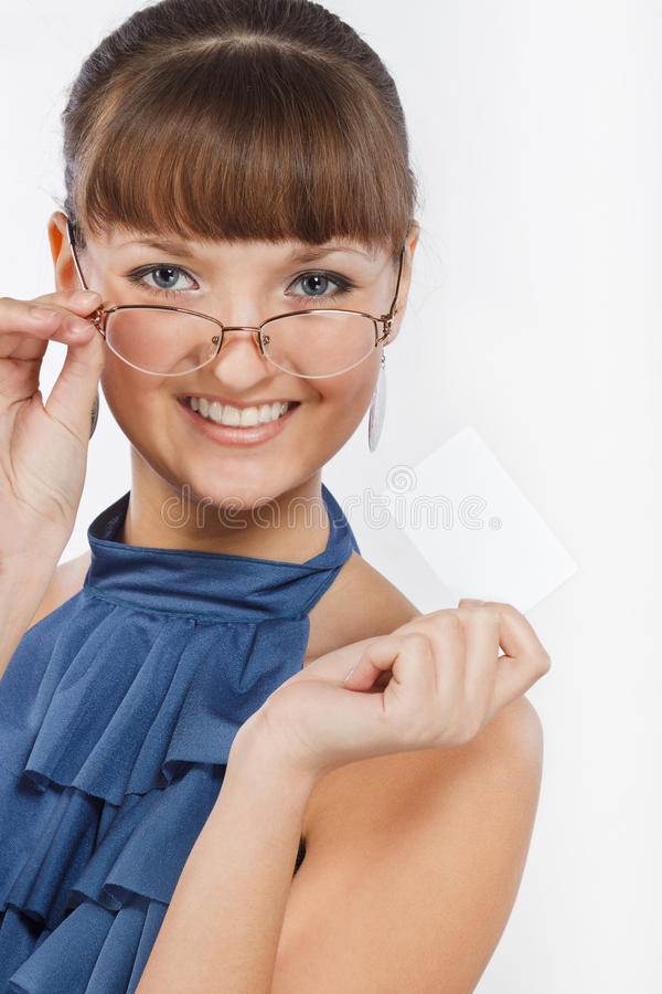 Young beautiful Smiling girl shows a business card. Young beautiful confident girl with glasses and in a blue blouse keeps a business card. She looks at the royalty free stock image