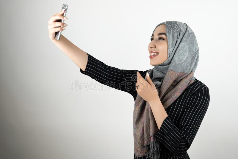 Young beautiful smiling happy Muslim woman in glasses wearing turban hijab, headscarf holding smartphone shooting a stock photography