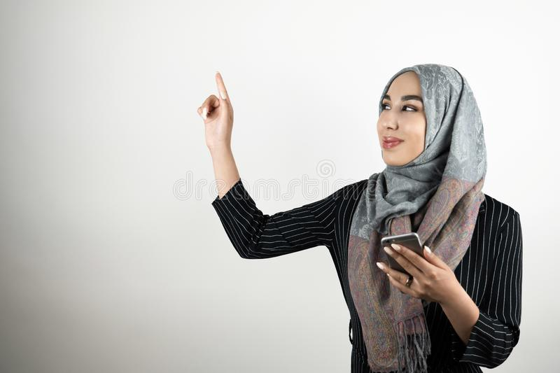 Young beautiful smiling Muslim business woman wearing turban hijab headscarf holding smartphone in one hand and pointing royalty free stock images