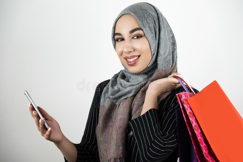 Young beautiful smiling Muslim business woman wearing turban hijab headscarf holding smartphone in one hand and shopping royalty free stock image