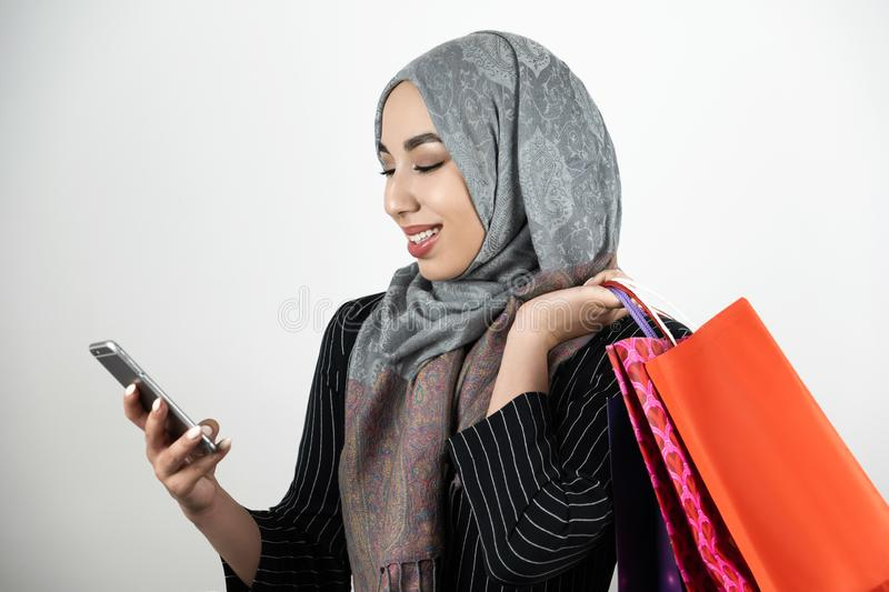 Young beautiful smiling Muslim business woman wearing turban hijab headscarf tapping smartphone with one hand and royalty free stock photography