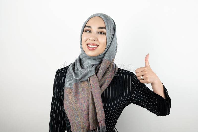 Young beautiful smiling positive Muslim woman wearing turban hijab headscarf showing ok sign isolated white background stock image