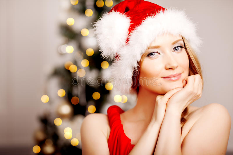 Young beautiful smiling santa woman near the Christmas tree. Fashionable luxury girl celebrating New Year. Beauty luxury trendy b royalty free stock photos