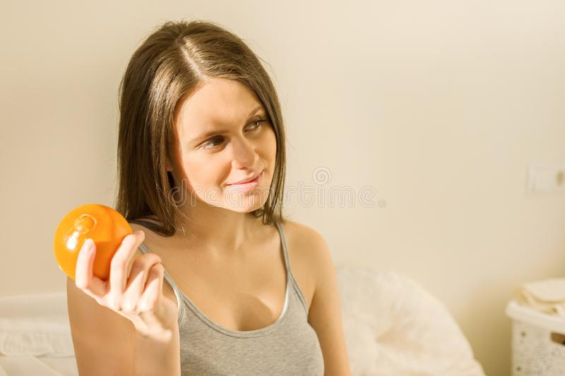 Young beautiful smiling woman holding an orange, at home sitting in bed stock images