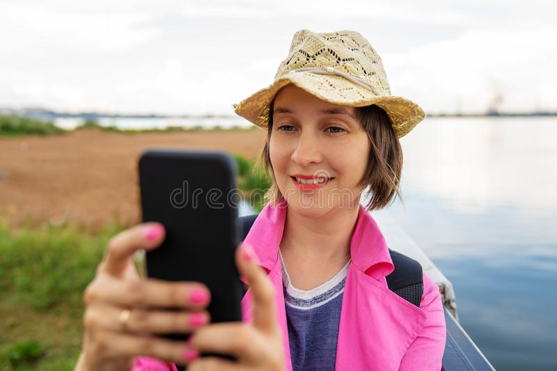 Young beautiful smiling woman is holding smart phone in hand and looking to the screen. Making selfie photo. Beach and a lake on a royalty free stock photos