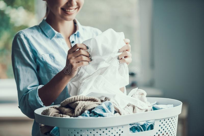 Young Beautiful Smiling Woman holds Clean Clothes. Closeup of Happy Beautiful Girl holding Fresh Clothing just after Laundry. Young Attractive Woman doing royalty free stock images