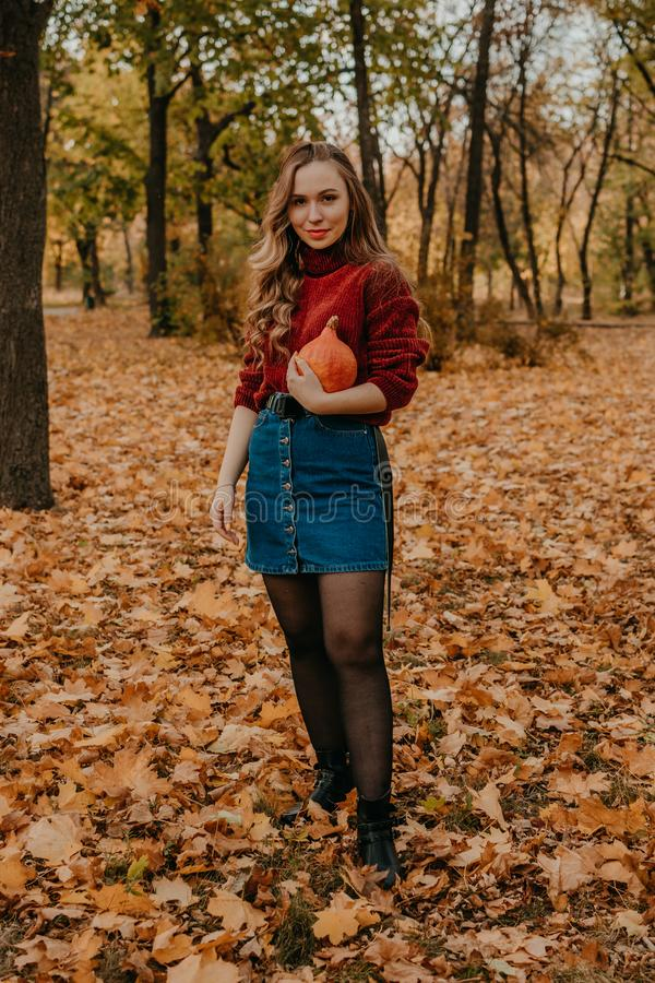 Young beautiful smiling woman with long curly hair holding orange halloween pumpkin on autumn park yellow trees background. Fall royalty free stock photography