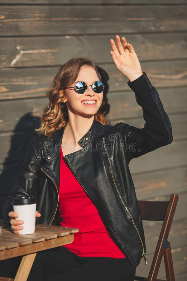 Young beautiful smiling woman in round glasses drinking coffee stock photos
