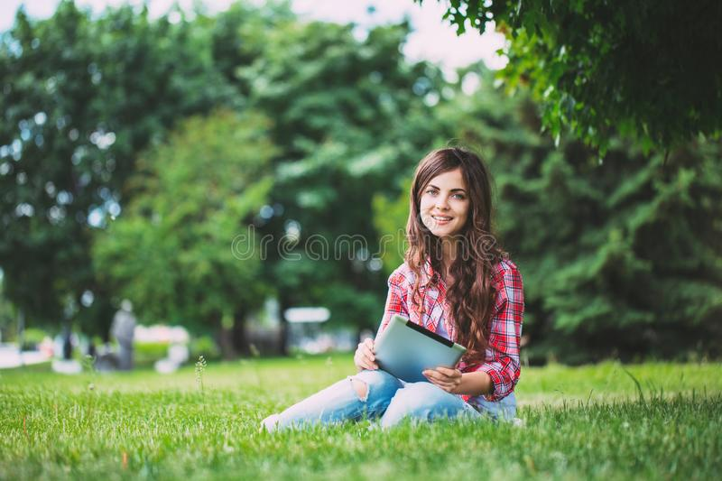 Young beautiful smiling woman with touchpad on outdoors royalty free stock image