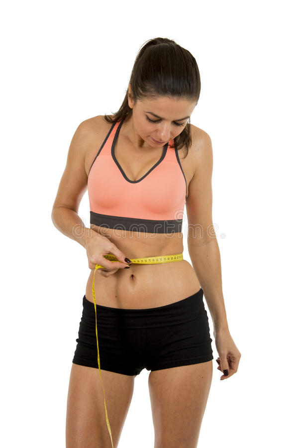 Young beautiful sport woman in fitness clothes measuring body waist size holding measure tape stock photography