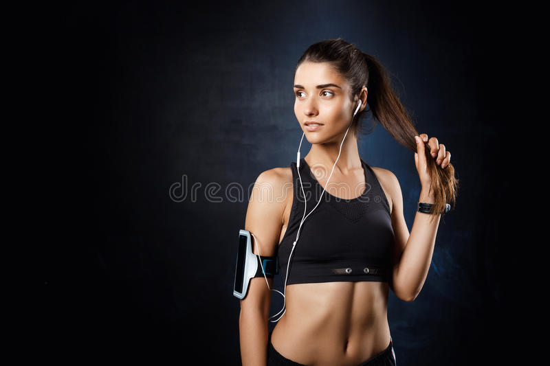 Young beautiful sportive girl listening music over dark background. Young beautiful brunette sportive girl listening music over dark background. Copy space royalty free stock photo