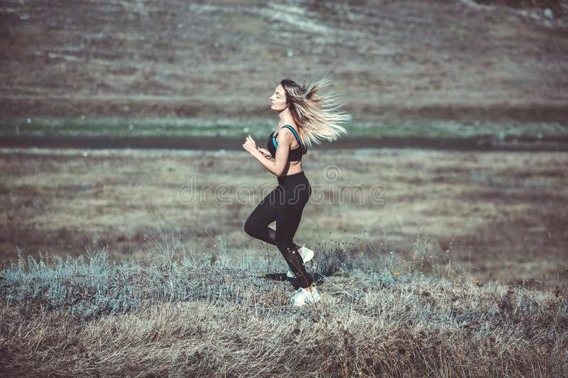 Young beautiful sportive girl runing. Girl is exercising. Outdoor sport. Beautiful strong sexy athletic caucasian fitness woman. Y stock photos