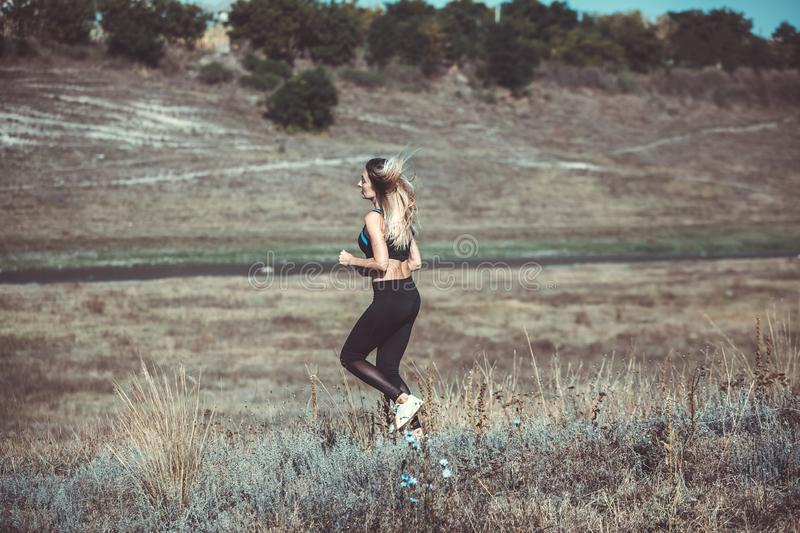 Young beautiful sportive girl runing. Girl is exercising. Outdoor sport. Beautiful strong sexy athletic caucasian fitness woman. Y stock photo