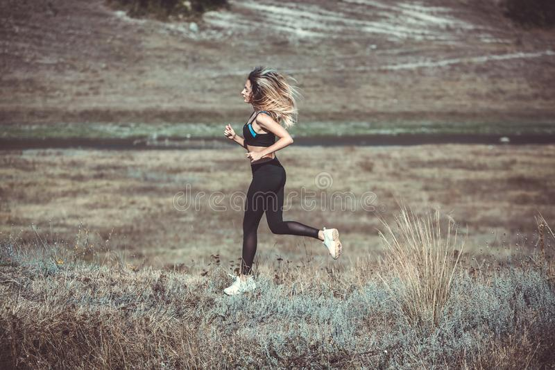 Young beautiful sportive girl runing. Girl is exercising. Outdoor sport. Beautiful strong sexy athletic caucasian fitness woman. Y royalty free stock photography
