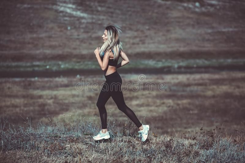 Young beautiful sportive girl runing. Girl is exercising. Outdoor sport. Beautiful strong sexy athletic caucasian fitness woman. Y royalty free stock photo
