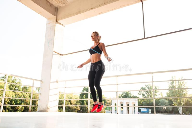 Young beautiful sports woman jumping with skipping rope royalty free stock photography