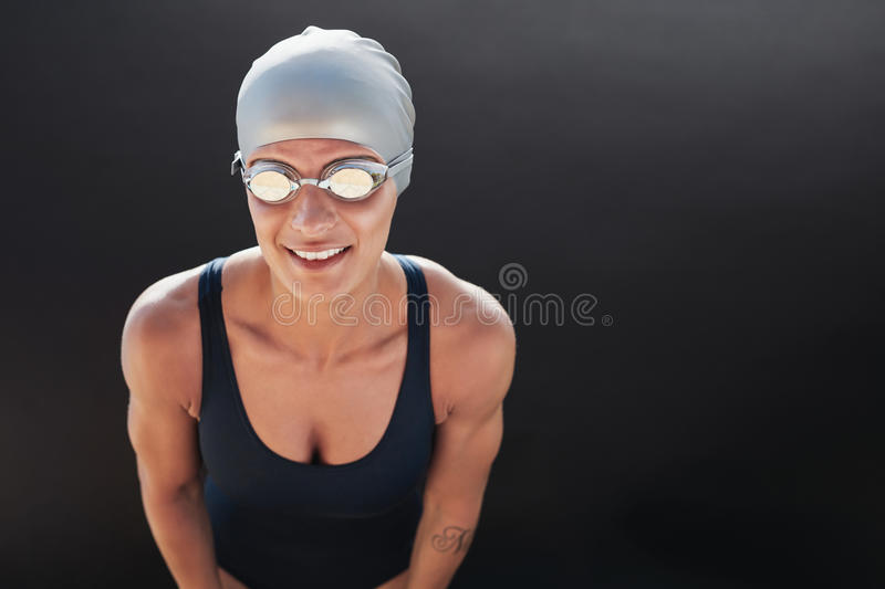Young beautiful sportswoman in swimsuit with swimming goggles. Looking at camera on black background stock images
