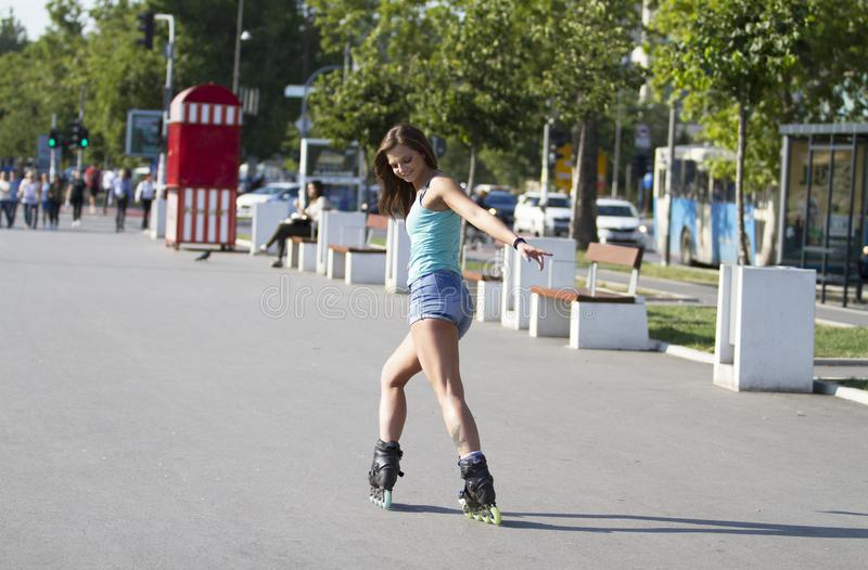 Young, beautiful, sporty and fit girl on inline skates. She drives on the street from behind. Beautiful, sporty and fit girl on inline skates. She drives on the royalty free stock images