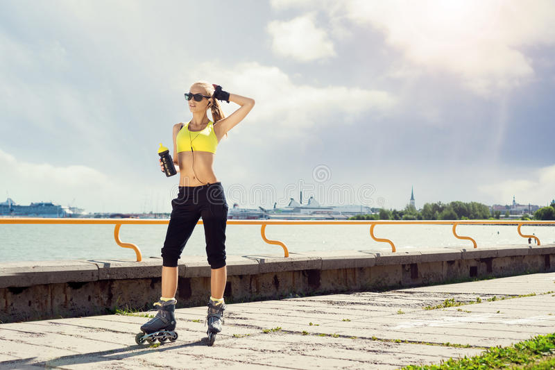 Young, beautiful, sporty and fit girl rollerblading on inline sk. Fit, sporty and athletic young woman. Beautiful girl rollerblading on skates in a sportswear royalty free stock image