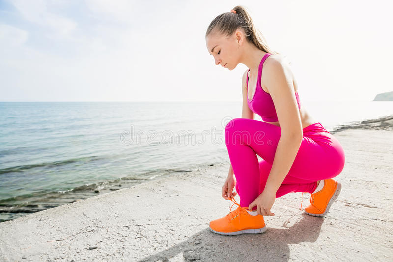 Young beautiful sporty girl in pink uniform on sea. Ties shoelaces stock images