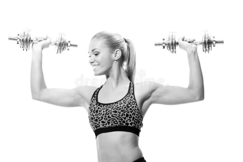Beautiful sporty woman working out with dumbbells royalty free stock photo