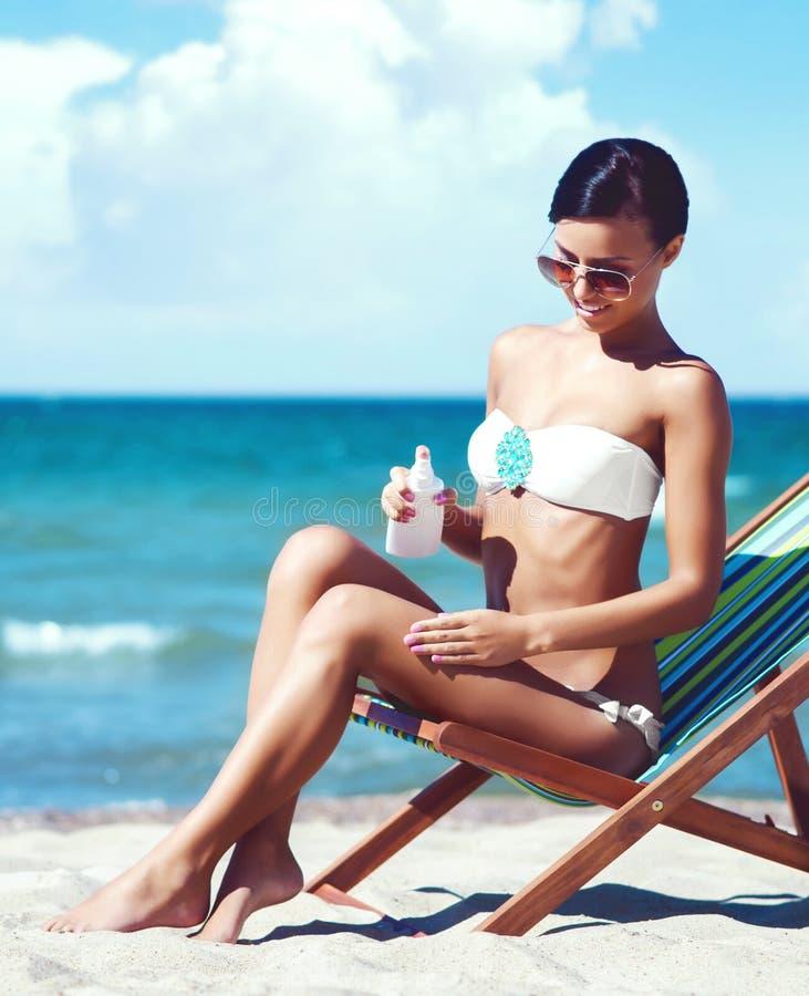 Young, beautiful, sporty and woman using the suntan cream o stock image