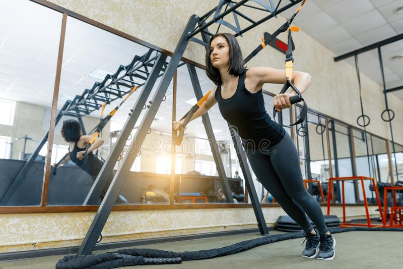 Young beautiful sporty woman exercising on fitness straps system in gym. Fitness, sport, training, and healthy lifestyle concept stock photos