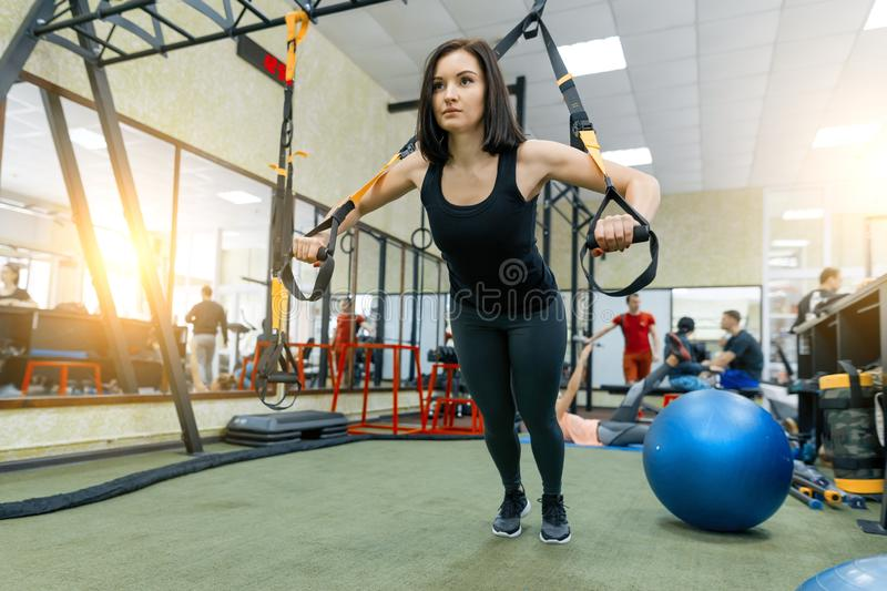 Young beautiful sporty woman exercising on fitness straps system in gym. Fitness, sport, training, and healthy lifestyle concept stock image