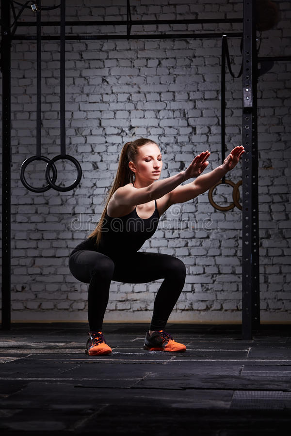 Young beautiful sporty woman making squats against brick wall in cross fit gym. royalty free stock image