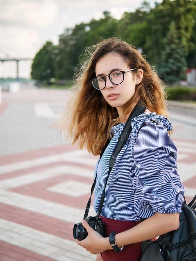 Young beautiful student girl in blue blouse and trendy glasses having fun with cup of coffee and photo camera posing on a river pi stock photography