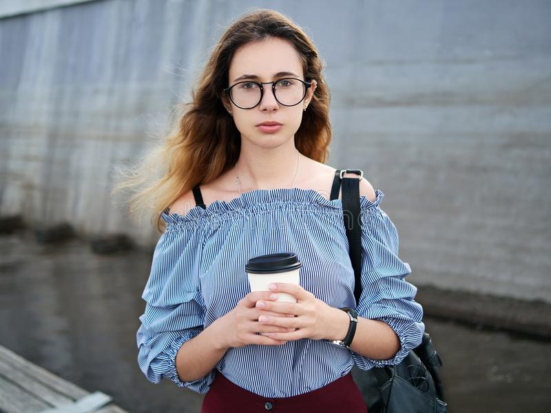 Young beautiful student girl in blue blouse and trendy glasses having fun with cup of coffee posing on a river pier in city park stock photo